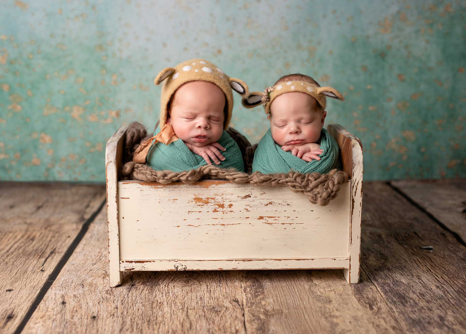 Baby twins are sitting next to each other with cute headbands during their session in Chicago photo studio
