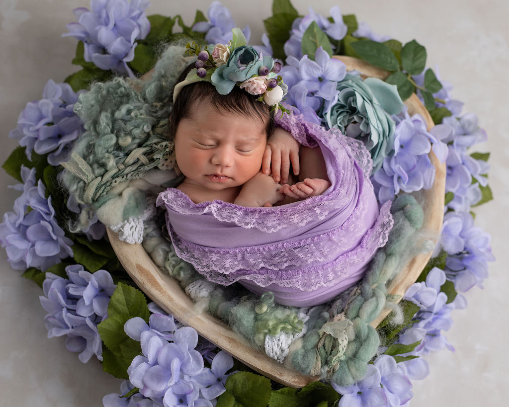 Newborn girl is being photographed as part of the family newborn session
