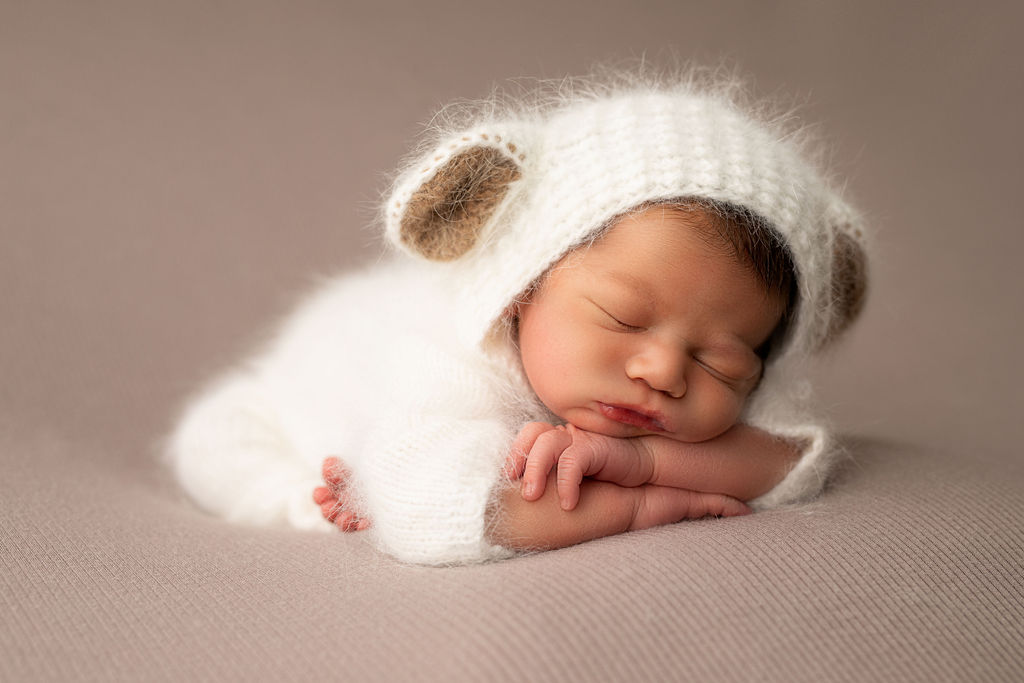 Cute little newborn is sleeping peacefully during his photography session