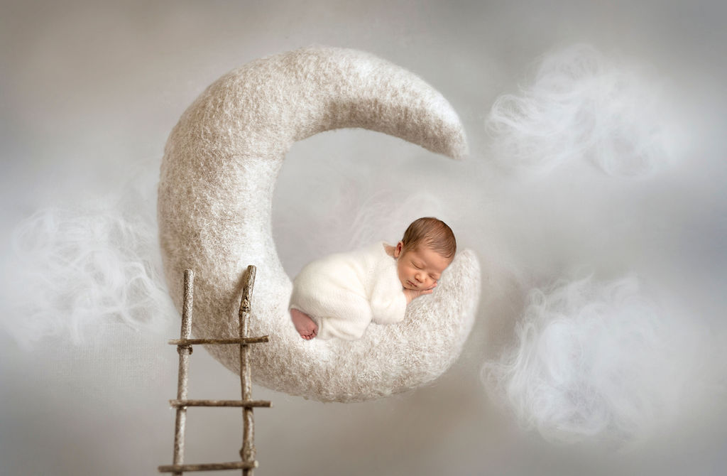 Artistic photo of the sleeping newborn on the moon