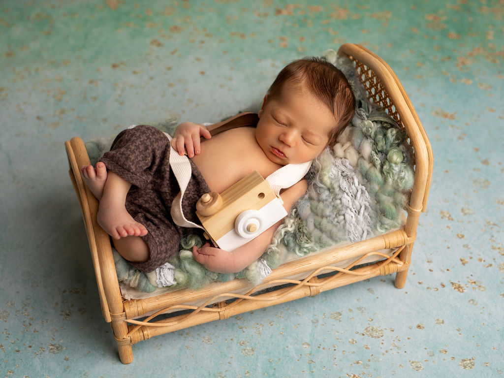 Amazing photo of the newborn with his cute photo camera during his family session in Chicago studio