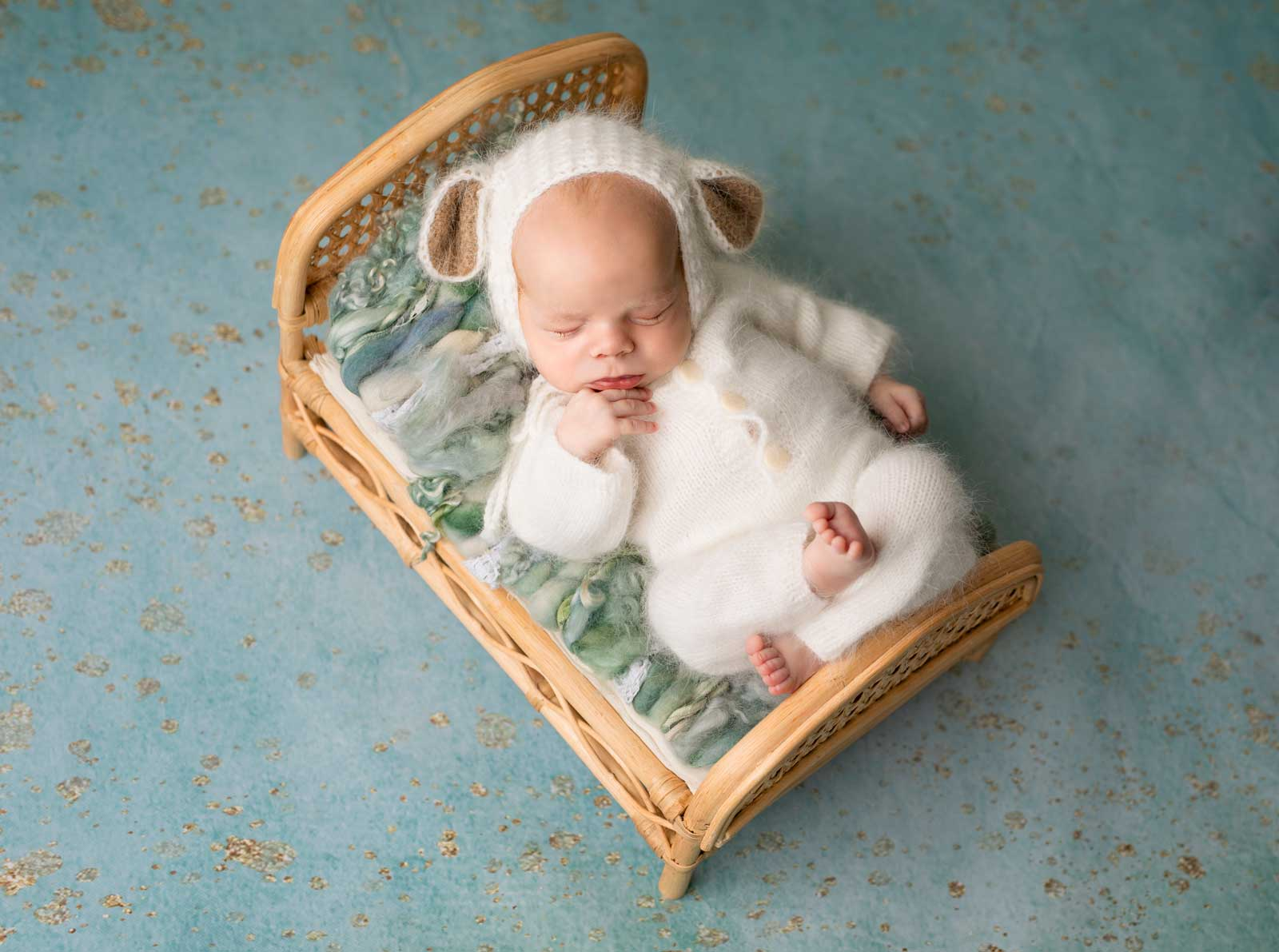 Baby boy is sleeping on a cute bed in a beautiful clothes provided by Photo studio in Chicago