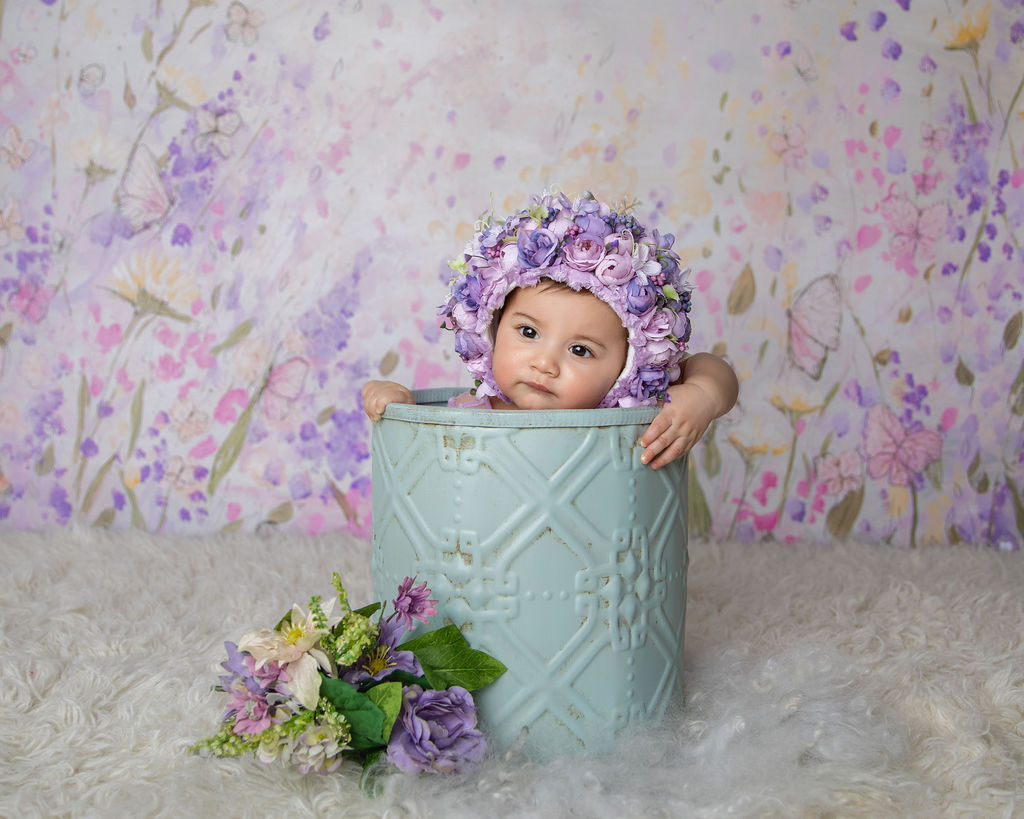 Amazing picture of the baby inside the basket and flowers near her